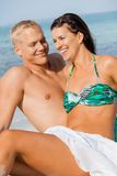 Happy young couple sunbathing. Happy attractive affectionate young couple sunbathing together on the beach in their swimwear while enjoying a tropical summer Stock Image