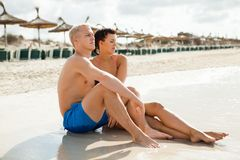 Happy young couple sunbathing. Happy attractive affectionate young couple sunbathing together on the beach in their swimwear while enjoying a tropical summer Royalty Free Stock Photography