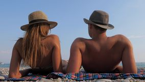 Happy Young Couple Sunbathing On Beach At The Seaside, Lying Down On The Back. Happy young couple in hats, sunbathing on the beach with a pebbly coastline, lying stock video