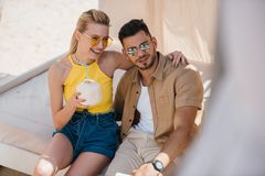happy young couple in sunglasses drinking summer cocktail while sitting together in bungalow stock photo