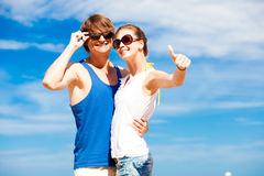 Happy young couple in sunglasses smiling pointing Royalty Free Stock Photography