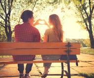 Happy young couple in sunny park. Happy young couple sitting on the bench in sunny park and making heart gesture together Royalty Free Stock Photos