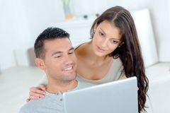 Happy young couple surfing on web at home Stock Photo