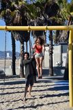Happy young couple on a swing set. Happy romantic couple playing on a swing set in a children's playground on the beach royalty free stock images