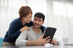 Happy Young couple with tablet. And laptop spending time together at their home on weekend stock photos