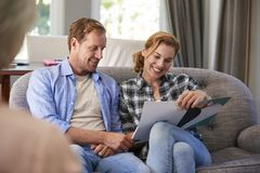 Happy young couple taking financial advice at home royalty free stock images