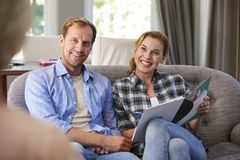 Happy young couple taking financial advice at home royalty free stock image