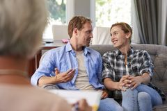 Happy young couple taking financial advice at home stock photos