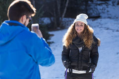 Happy young couple taking photos over winter background. Stock Image