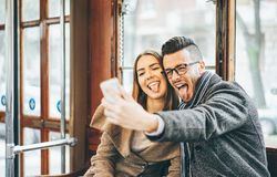 Happy young couple taking photos using mobile smart phone camera inside bus - Travel lovers making a self portrait to post. Happy young couple taking photos royalty free stock photos