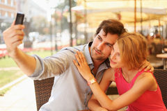 Happy young couple taking self portrait in cafe Stock Photo