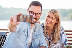 Happy young couple taking a selfie in a cafe stock images