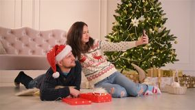 Happy Young Couple Taking Selfie In Decorated For Christmas Room. Happy New Year Concept. Lovely Family. HD, Good Mood, Christmas Tree stock video