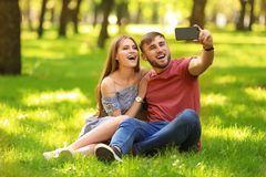 Happy young couple taking selfie on green grass in park Stock Photography