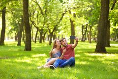 Young couple taking selfie on green grass in park Stock Photography