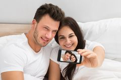 Happy young couple taking a selfie Stock Photography