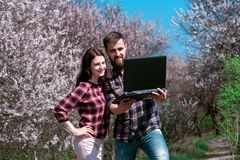 Happy young couple taking selfie in the park02. Couple of young people looking in laptop standing in a blooming spring park Stock Photos