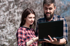 Happy young couple taking selfie in the park01. Couple of young people looking in laptop standing in a blooming spring park Stock Photos