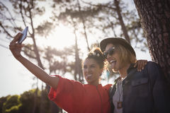 Happy young couple taking selfie while standing together Royalty Free Stock Photography