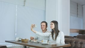 Happy young couple taking selfies with food on smartphone at a restaurant stock images
