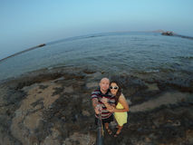 Happy, young couple taking selfy on the beach Stock Photography