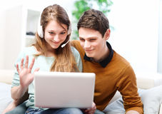 Happy young couple talking through the computer with video chat Royalty Free Stock Photos