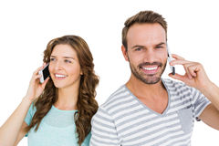 Happy young couple talking on mobile phone Stock Photography