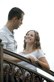 Happy young couple talking on outdoor balcony. Beautiful young couple talking and smiling on outside balcony . shot on an overcast day from a low angle making Royalty Free Stock Image