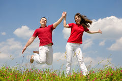 Happy Young Couple - team is jumping Stock Photos