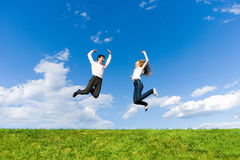 Happy Young Couple - team is jumping in the sky. Above a green meadow Royalty Free Stock Photo
