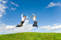 Happy Young Couple - team is jumping in the sky. Above a green meadow Stock Image