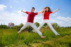 Happy Young Couple - team is jumping in the sky. Above a green meadow Royalty Free Stock Images
