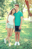 Happy young couple teenagers stands on the grass royalty free stock images