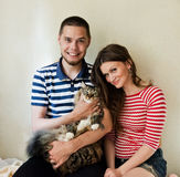 Happy young couple with their cat Royalty Free Stock Images