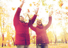 Happy young couple throwing autumn leaves in park Royalty Free Stock Images