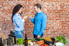 Happy Young Couple Toasting with White Wine Stock Images