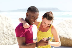 Happy young couple together at the beach using mobile phone Stock Image