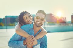 Happy young couple toothy smile in piggyback pose at oudoors stock photos