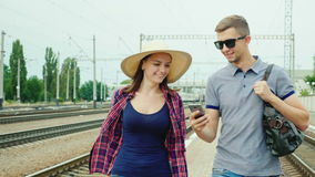 Happy young couple of tourists with a smartphone goes to the train station. Concept: order online tickets. Steadicam shot stock footage