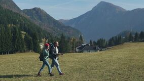 Happy young couple of travelers hiking with map and looking area. Millennials with backpack traveling highlands on