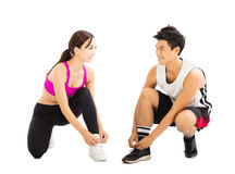 Happy young couple tying sports shoes Royalty Free Stock Photos