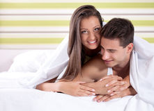 Happy young couple under covers in bed Royalty Free Stock Photo