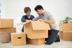 Couple unpacking cardboard boxes at new home. Moving house. Happy Young Couple unpacking cardboard boxes at new home. Moving house royalty free stock photos