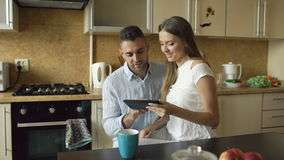 Happy young couple using digital tablet computer while sitting in the kitchen and having breakfast in the morning stock video