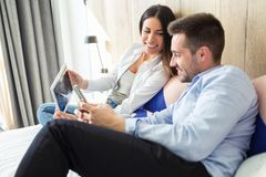Happy young couple using digital tablet and mobile phone while sitting on the bed in the hotel room stock images