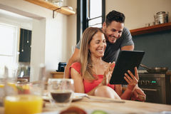 Happy young couple using a digital tablet in morning. Happy young couple in the modern kitchen in the morning, using a digital tablet. Smiling young women Stock Photo