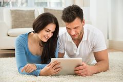 Happy young couple using digital tablet Stock Photos