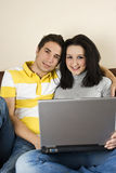Happy young couple using laptop. Happy young couple sitting in embrace  on a sofa and  using laptop in  their home,see more in People on couch Royalty Free Stock Images