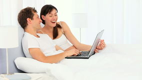 Happy young couple using a laptop. In the bedroom stock video