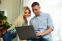 Happy young couple using laptop. At home Royalty Free Stock Photo